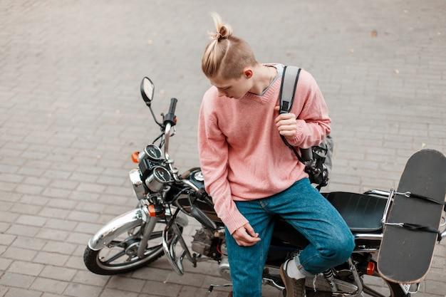 Красивый молодой человек в стильной одежде с рюкзаком и со скейтбордом сидит на мотоцикле