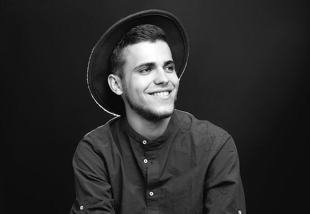 Красивый молодой человек в стильной шляпе на черном, черном и белом