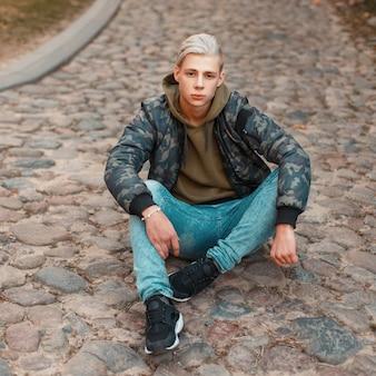 청바지가 바닥에 앉아 세련된 군사 재킷에 잘 생긴 젊은 남자