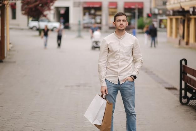 市内のハンサムな若い男は、クラフトパッケージで立っています。
