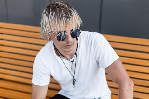 목에 부적과 세련 된 블루 선글라스에 유행 흰색 티셔츠에 잘 생긴 젊은 남자는 야외 나무 벤치에 앉아있다. 미국 도시 녀석은 금발이 도시에서 이완합니다. 스트리트 스타일