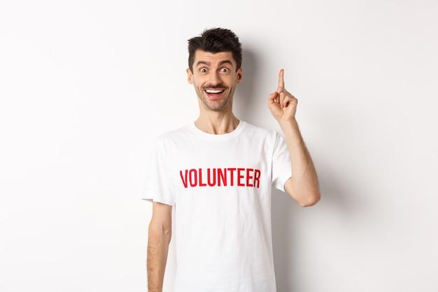 Красивый молодой человек в футболке добровольца, имеющий идею, поднимающий палец и говорящий предложение, указывая вверх, стоя над белым.