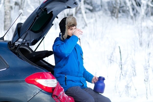暖かい冬の服を着たハンサムな若い男は、座っている魔法瓶から熱い飲み物のお茶やコーヒーを飲んでいます
