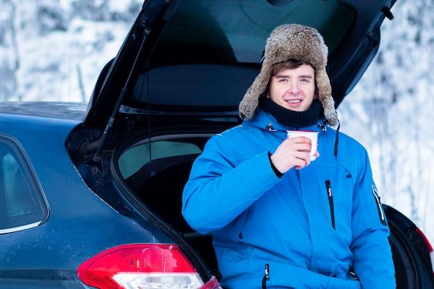 Красивый молодой человек в теплой зимней одежде пьет горячий напиток, чай или кофе