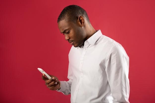 Красивый молодой человек в белой рубашке с телефоном