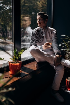 明るい窓の前に窓の上に刺繍と白いスーツのハンサムな若い男が座っている