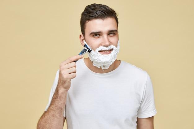白いtシャツを着たハンサムな若い男が、顔のケアをしながら、笑顔で肌の炎症を避けるために、髭を穀物に剃りながらかみそりを持っています。男らしさ、スタイル、美しさ