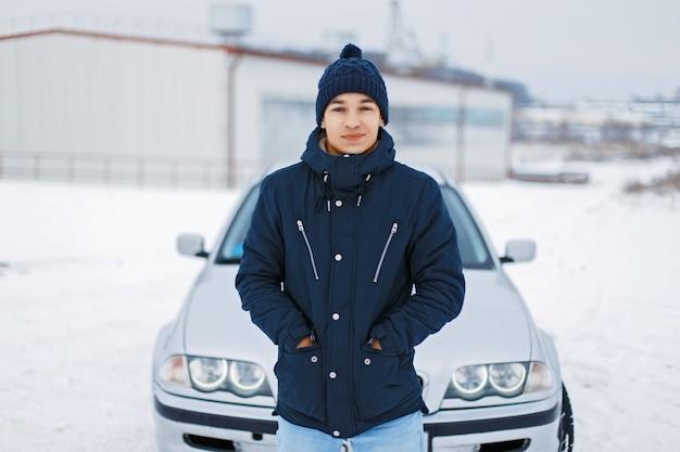 겨울 재킷과 니트 모자에 잘 생긴 젊은 남자는 차 근처에 서