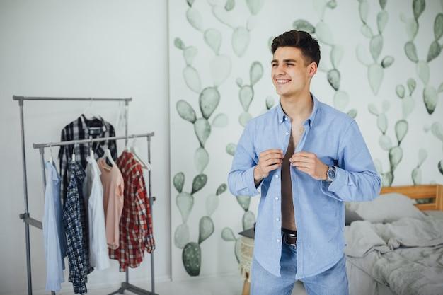 ハンサムな若い男は、家で服を着ている間、彼の白いシャツをボタンで留めています。