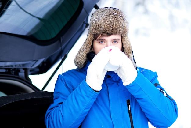 Красивый молодой человек пьет горячий напиток чай или кофе из кружки в перчатках и зимней одежде