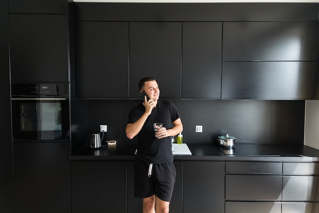 Handsome young man is drinking water, talking on the mobile phone and smiling while standing in kitchen at home