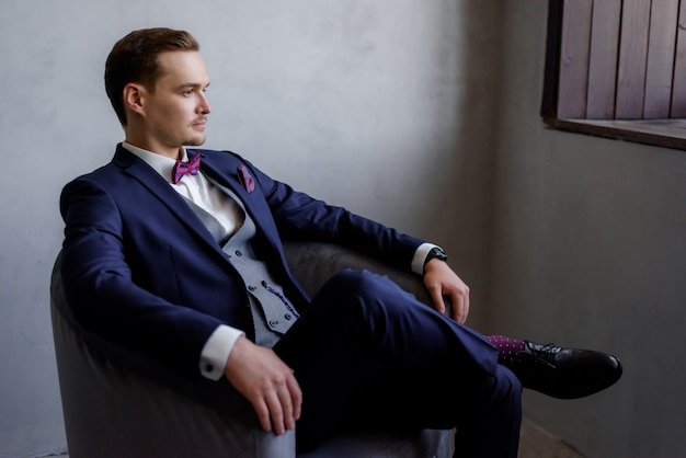 Handsome young man is sitting in the armchair in the room, dressed in the fashionable suit