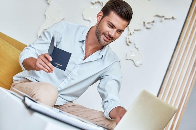 ハンサムな若い男は、ラップトップとパスポートを持って旅行代理店に座っています
