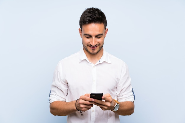Handsome young man over isolated blue sending a message with the mobile