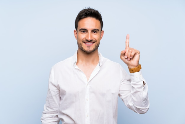 Handsome young man over isolated blue showing and lifting a finger in sign of the best