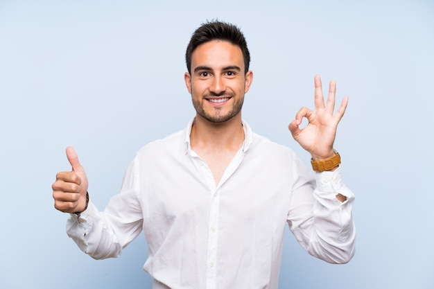 Handsome young man over isolated blue showing ok sign and thumb up gesture