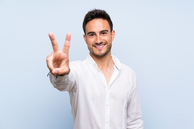 Handsome young man over isolated blue smiling and showing victory sign