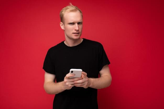 배경 벽 너머로 격리된 잘생긴 청년은 일상적인 옷을 입고 카메라를 바라보며 문자 메시지를 작성하는 휴대폰을 사용합니다.