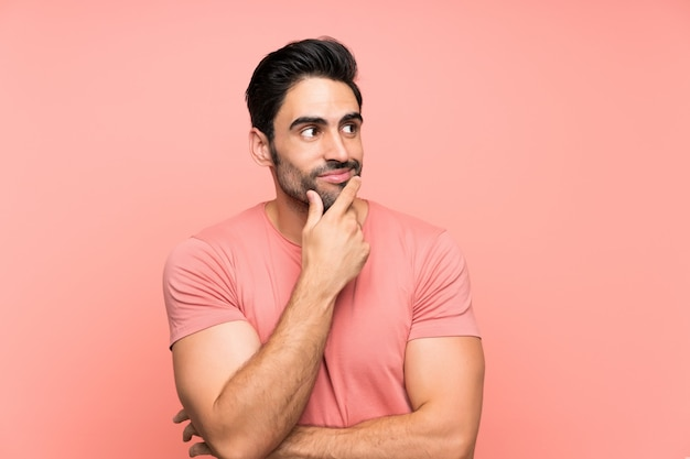 Handsome young man over isolated pink background thinking an idea
