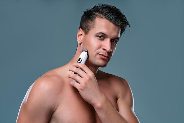 孤立したハンサムな若い男。上半身裸の筋肉の男の肖像画は、剃っている間、手にトリマーと灰色の背景に立っています。マンケアのコンセプト。