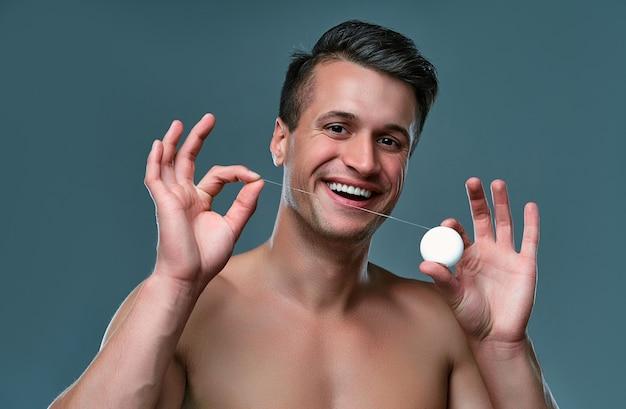 Красивый молодой человек изолирован. портрет мускулистого мужчины без рубашки стоит на сером фоне с зубной нитью в руках. концепция ухода за мужчинами.
