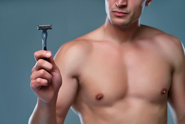 孤立したハンサムな若い男。上半身裸の筋肉の男の肖像画は、手にかみそりを持って灰色の背景に立っています。男性のケアの概念。