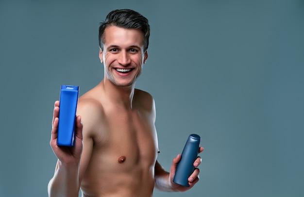 孤立したハンサムな若い男。上半身裸の筋肉の男の肖像画は、シャンプーを手に灰色の背景に立っています。男性のケアの概念。
