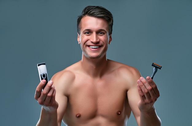 孤立したハンサムな若い男。上半身裸の筋肉の男の肖像画は、片方の手にトリマーともう片方の手にかみそりで灰色の背景に立って笑っています。男性のケアの概念。