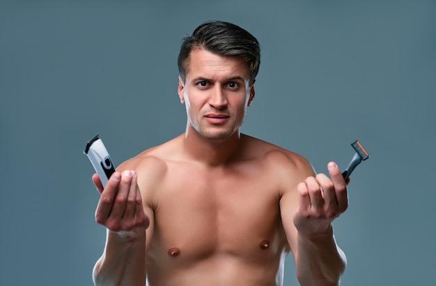 孤立したハンサムな若い男。上半身裸の筋肉の男の肖像画は、片方の手にトリマーともう片方の手にかみそりで灰色の背景に立っています。男性のケアの概念。