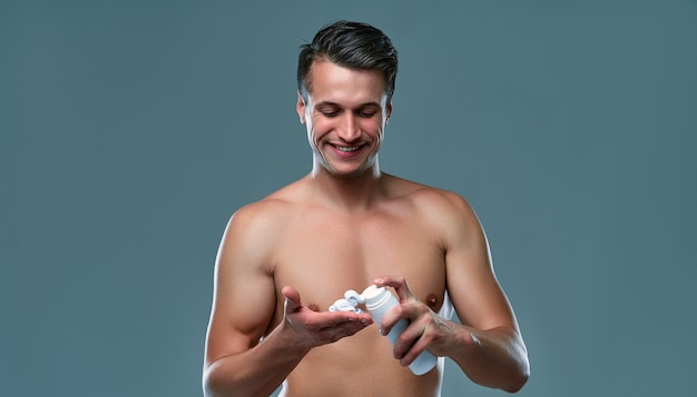 Handsome young man isolated. portrait of shirtless muscular man is standing on grey background squeezes shaving foam into the palm of his hand. men care concept.