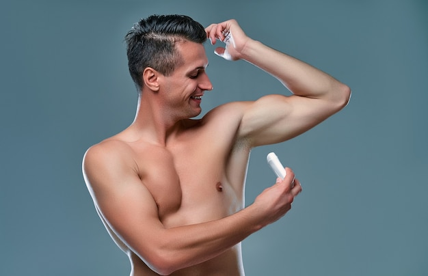 Handsome young man isolated. portrait of shirtless muscular man is standing on grey background and using antiperspirant. men care concept.
