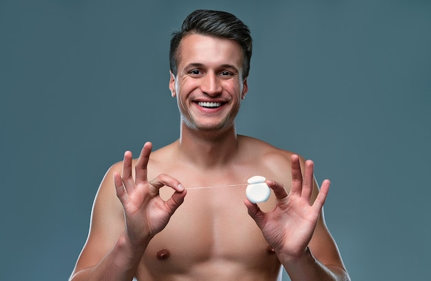 Handsome young man isolated. portrait of shirtless muscular man is standing on grey background with  dental floss in hands. men care concept.