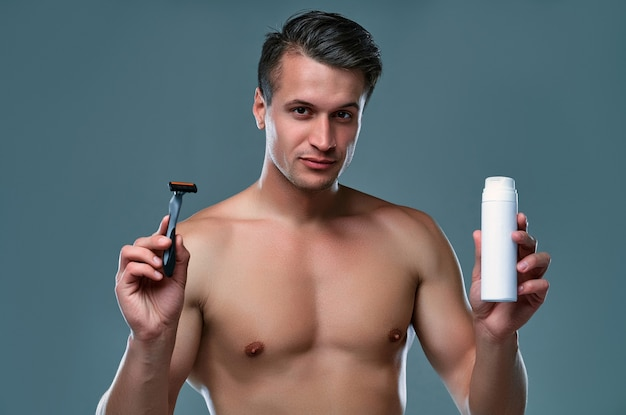 Handsome young man isolated. portrait of shirtless muscular man is standing on grey background with razor in hand and shaving foam. men care concept.