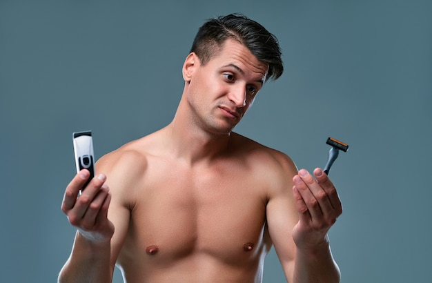 Handsome young man isolated. portrait of shirtless muscular man is standing on grey background with trimmer in one hand and razor in other. men care concept.
