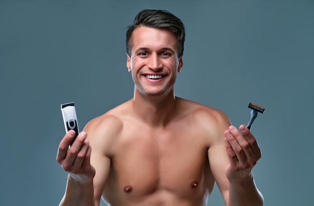 Handsome young man isolated. portrait of shirtless muscular man is standing on grey background with trimmer in one hand and razor in other and smiling. men care concept.