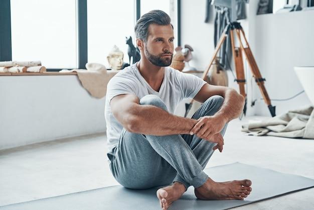Красивый молодой человек, держащий ноги вместе, занимаясь фитнесом дома