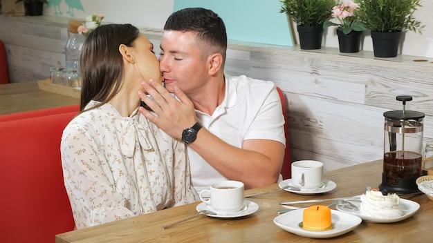 ハンサムな若い男は、カフェでお茶とおいしいケーキを添えてテーブルでデート中に美しいガールフレンドにキスします