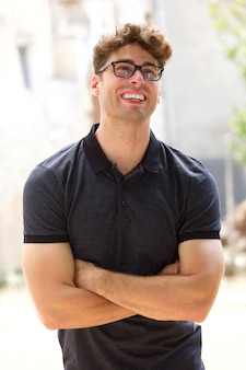 Handsome young man laughing with glasses outdoors