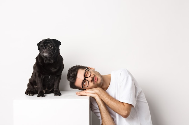 Handsome young man lay head near cute black pug, smiling and looking up at copy space, white