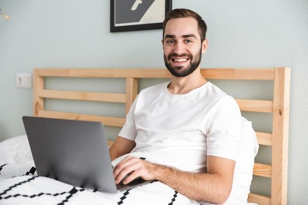 Красивый молодой человек, лежа в постели, работая на портативном компьютере