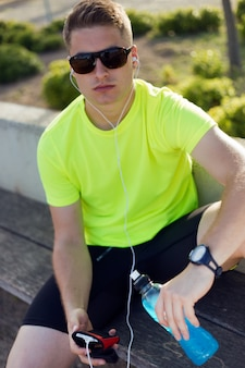 Handsome young man listening to music after running.