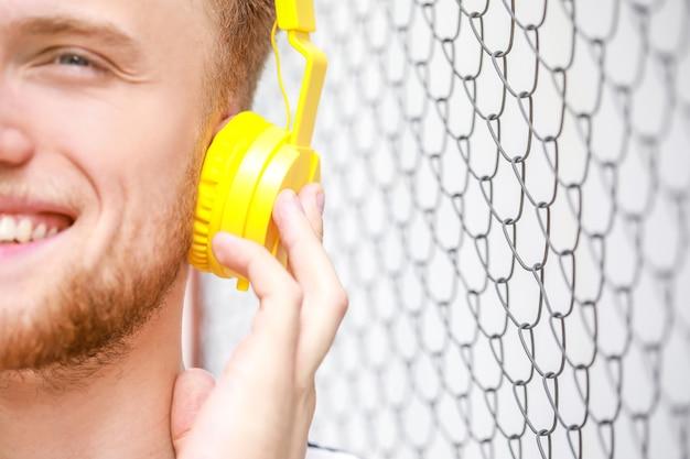 屋外で音楽を聴いているハンサムな若い男、クローズアップ