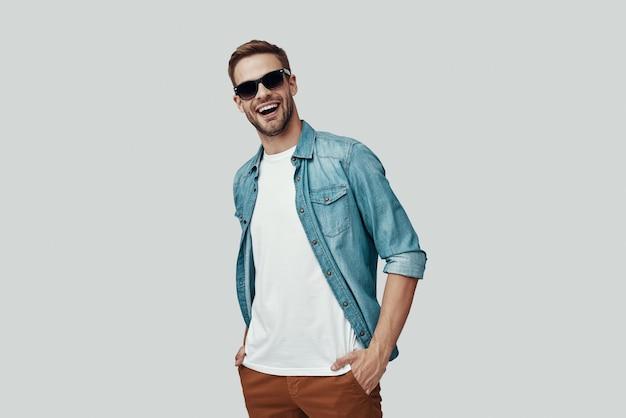 カメラを見て、灰色の背景に立って笑っているハンサムな若い男