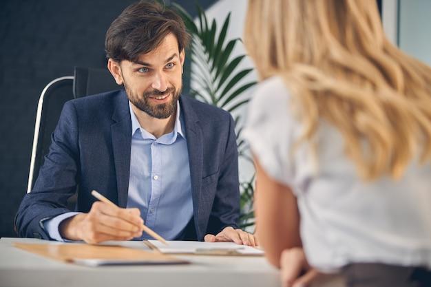 女性のビジネスパートナーを見て、テーブルに座ってクリップボードを指して笑っているハンサムな若い男