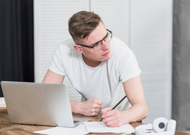 Handsome young man looking away writing on paper with pencil and laptop on table