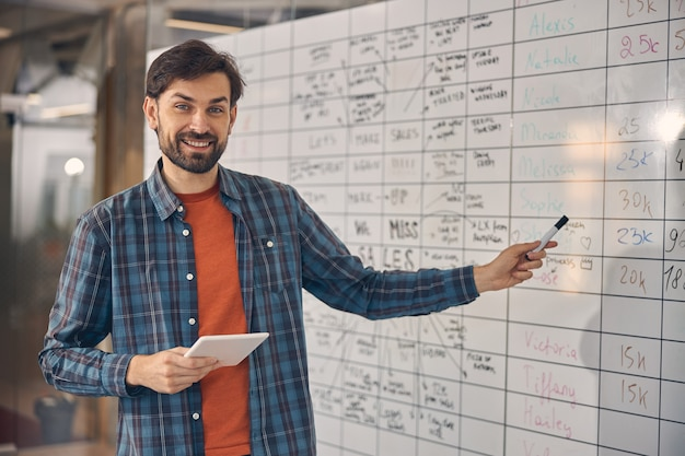 Handsome young man looking at camera and smiling while standing by planner board and holding electronic pad pc