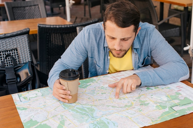 Handsome young man looking at map with holding coffee cup in caf�