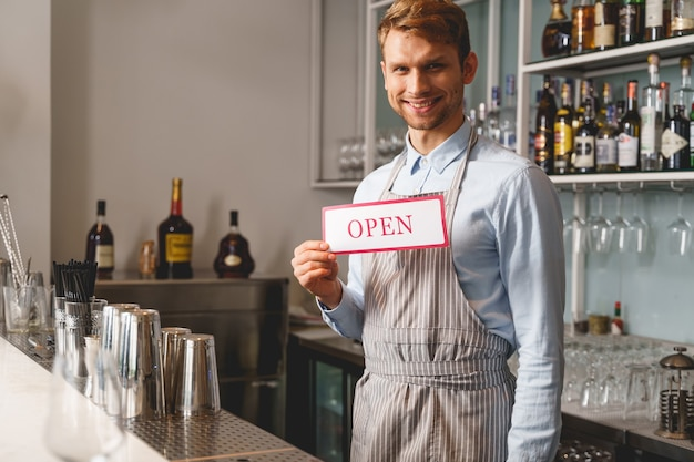 Handsome young man looking and smiling while demonstrating signboard with word open