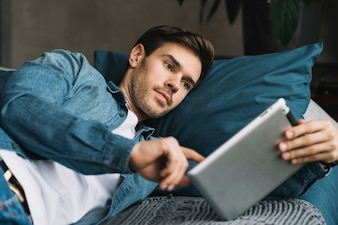 Handsome young man lying on bed using digital tablet