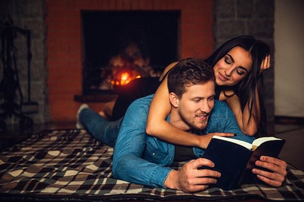 ハンサムな若い男は床に横たわって、開いた本を読みます。彼のガールフレンドは彼の上にも見てください。彼らは暖炉の近くで時間を過ごします。